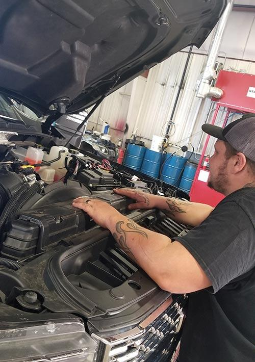 heavy equipment mechanic inspecting under the hood of a commercial truck for repair analysis